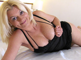 Blonde mature slut playing with herself on the bed