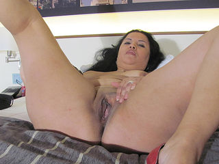 Kinky mature slut playing on her bed with a dildo