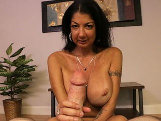 Top heavy step mom Nadia Night wants to jerk and milk your pulsating cock. She pulls down her top and exposes her massive fake tits and hard nipples glide your cockhead. This milf is horny as fuck and wants to see you cum with her soft and slow rubbing. She focuses on your cock head and she doesnt stop until your spurt you goo.